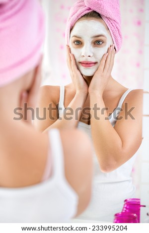 Beauty day, young girl  with a towel on her head and  cosmetic mask