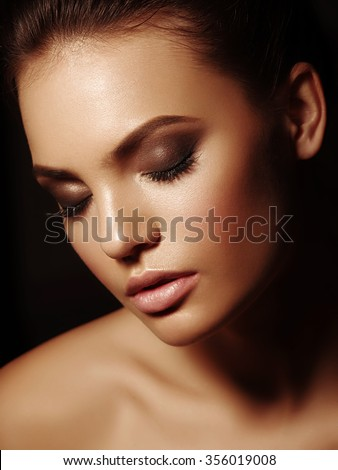 Beauty elegant portrait of a sexy appealing naked brunette with full lips and closed eyes on the black background
