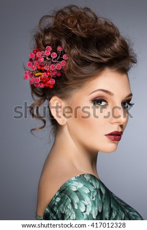 Beauty face. Girl with flowers in her hair. The girl's face. Red flowers. Pretty brunette female model face with artistic make up.