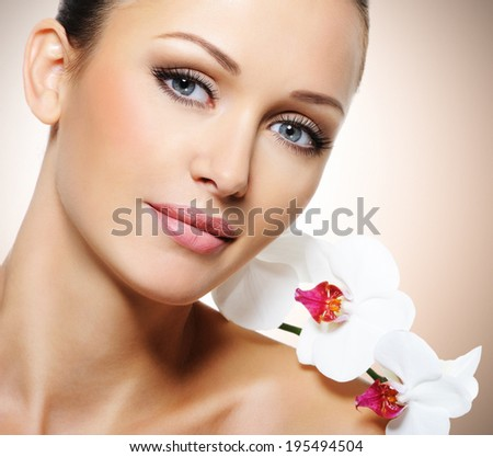 Beauty face of  beautiful woman with a white flower. Skin care treatment. - stock photo