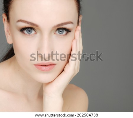 Beauty face of beautiful woman with clean fresh skin-gray background - stock photo