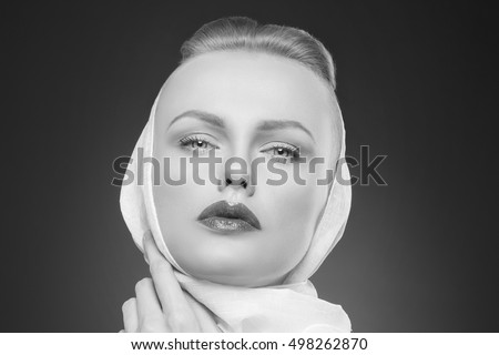 Beauty face of caucasian blonde woman with natural make-up and red lips wearing white shawl over dark background. Studio portrait. Black and white