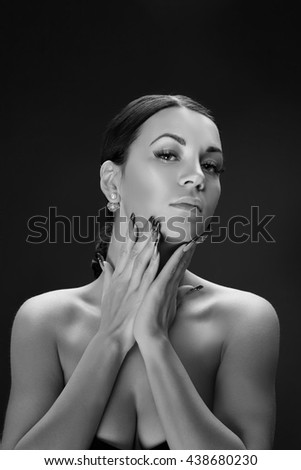 Beauty face of caucasian brunette woman with perfect nails. Isolated on black background. Black and white - stock photo