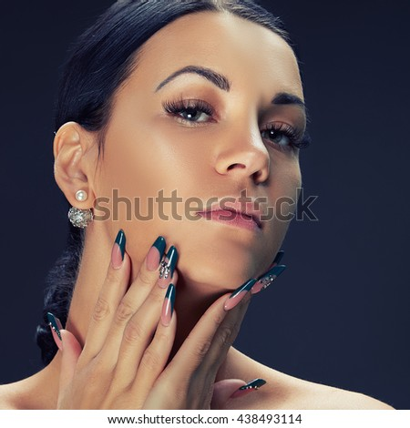 Beauty face of caucasian brunette woman with perfect nails. Isolated on black background. Toned - stock photo