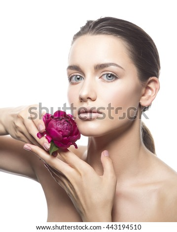 Beauty face of caucasian brunette young woman posing with peony flower in hands. Studio portrait. Isolated on white background.