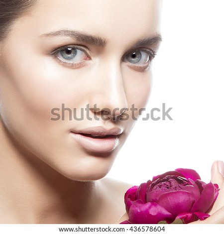 Beauty face of caucasian young brunette woman with peony flower in hand. Studio portrait. Isolated on white background.  - stock photo