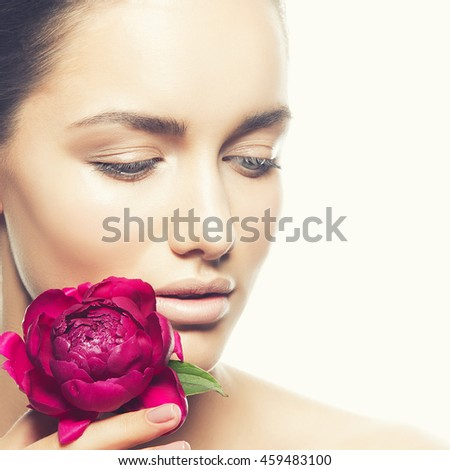 Beauty face of caucasian young brunette woman with peony flower in hand. Studio portrait. Isolated on white background. Toned. - stock photo