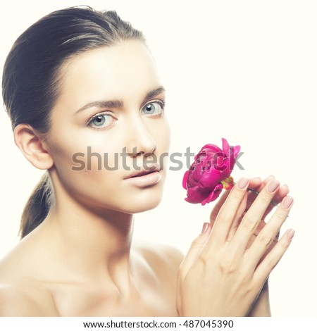 Beauty face of caucasian young brunette woman with peony flower in hand. Studio portrait. Isolated on white background. Toned