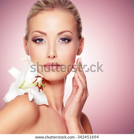 Beauty face of the young beautiful girl with flower. Female touching skin.