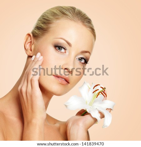 Beauty face of the young beautiful woman with flower - stock photo