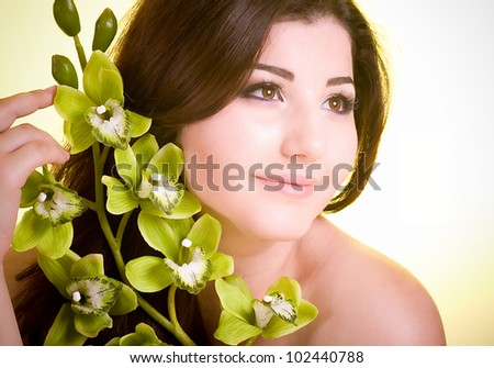 Beauty face of the young woman with flower on color background - stock photo