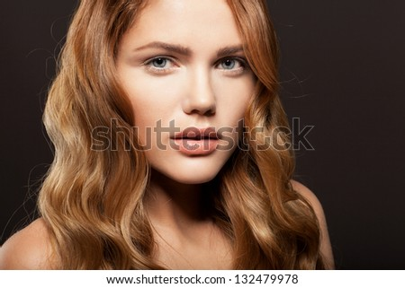 Beauty face of woman with clean fresh skin and long golden hair on dark background