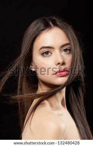 Beauty face of woman with clean fresh skin and long hair on dark background - stock photo