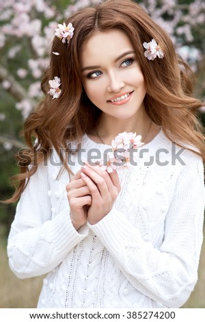 Beauty face of young beautiful woman with pink  almond flowers in her hair. Spring woman portrait.  - stock photo