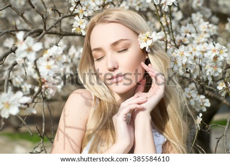 Beauty face of young beautiful woman with pink almond flowers in her hair. Spring woman portrait