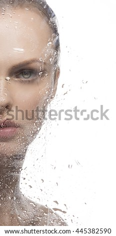Beauty face of young caucasian blonde woman behind glass with water drops.