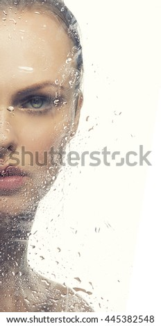 Beauty face of young caucasian blonde woman behind glass with water drops. Toned