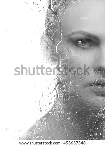 Beauty face of young caucasian woman near a mirror with water drops. Studio portrait. Isolated on white background. Black and white