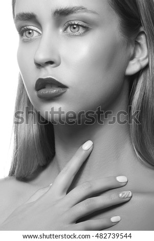 Beauty face of young girl with maroon lipstick and hand near lips looking at camera isolated on white background. Studio portrait. Black and white