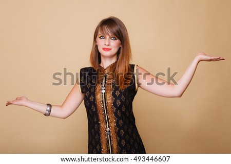 Beauty, fashion, advertisement concept. Orient eastern girl with perfect makeup. Woman in traditional indian clothing holding open palms, empty hands copy space for product on brown