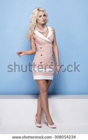 beauty, fashion and young woman in pink dress on blue background - stock photo