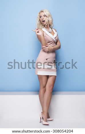 beauty, fashion and young woman in pink dress on blue background pointing her finger to the side empty space - stock photo