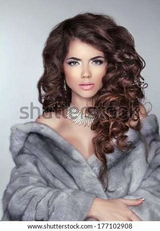 Beauty Fashion Brunette model girl wearing in Blue Mink Fur Coat. Beautiful Luxury Winter Woman. Wavy long healthy hair. - stock photo