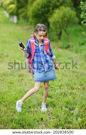 Beauty  fashion brunette school age kid girl in the blue plaid shirt, jeans skirt and yellow scarf writing in her notepad outdoor on the playground - stock photo