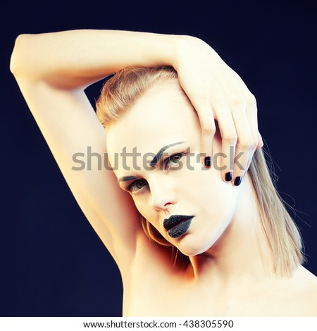 Beauty fashion caucasian model girl with black make up and dark lipstick. Isolated on black background. Toned