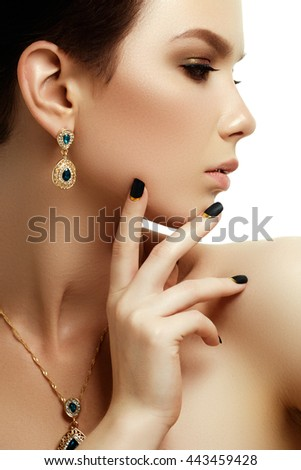 Beauty & fashion concept. Beautiful woman with jewelry, close-up. Beauty portrait of the fashion model with golden manicure and perfect skin - stock photo