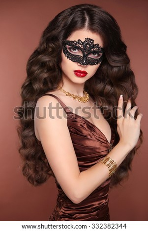 Beauty fashion elegant brunette woman. Healthy long wavy hair style. glamour lady wearing in venetian masquerade carnival mask and evening dress.