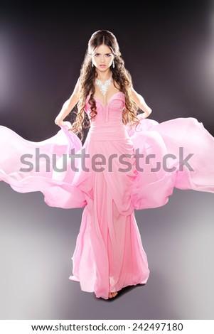 Beauty fashion girl model posing in pink blowing transparent chiffon dress over dark lights background. Diamond Jewelry.  - stock photo