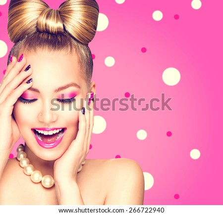 Beauty fashion happy model girl with funny bow hairstyle, pink nail art and makeup over polka dots background. Laughing retro styled young woman - stock photo