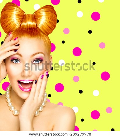 Beauty fashion happy model girl with funny bow hairstyle, pink nail art and makeup over polka dots green background. Red hair. Laughing retro styled young woman - stock photo