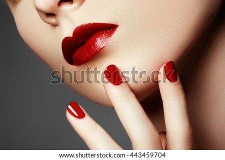 Beauty fashion model face. Manicured hand with red nails. Red lips and nails. Beautiful woman with luxury make-up and perfect manicure. Make-up concept