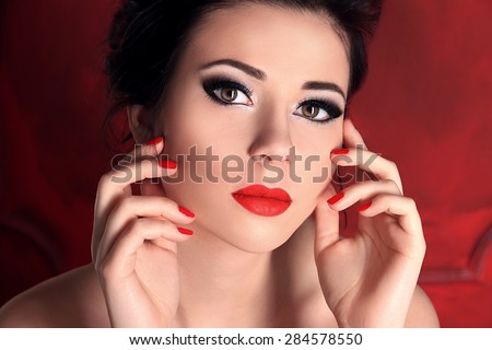 Beauty Fashion Model Girl Closeup Portrait over Red Background. Young Woman with Perfect Skin, Smoky Eyes Makeup, Long Eyelashes, Red Lips and Nails.