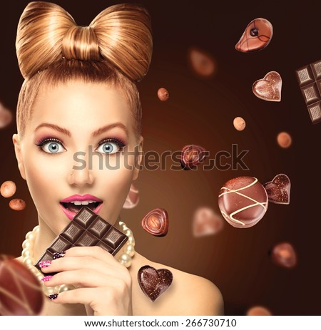 Beauty fashion model girl eating chocolate. Beautiful Surprised young woman takes chocolate sweets. Funny girl, professional make up and bow hairstyle. Diet,dieting concept - stock photo