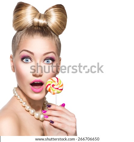 Beauty fashion model girl Eating colourful lollipop. Surprised Young funny woman with bow hairstyle, pink nail art and makeup isolated on white background - stock photo