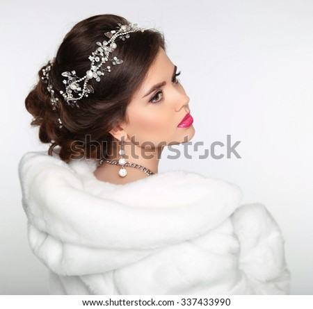 Beauty Fashion Model Girl in white Mink Fur Coat. Wedding hairstyle. Beautiful Luxury Winter Woman isolated on white background. - stock photo