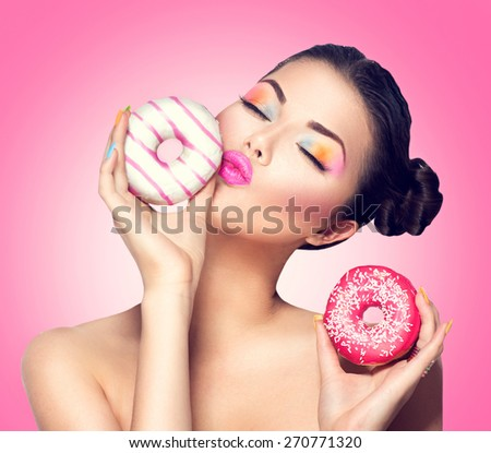 Beauty fashion model girl taking kissing colorful donuts. Funny joyful Vogue styled woman choosing sweets on pink background. Diet, dieting concept. Junk food, Slimming, weight loss - stock photo