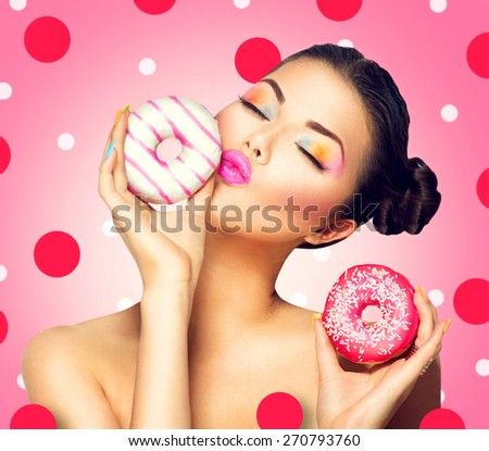 Beauty fashion model girl taking sweets and colorful donuts. Funny joyful Vogue styled woman choosing sweets on pink background. Diet, dieting concept. Junk food, Slimming, weight loss - stock photo