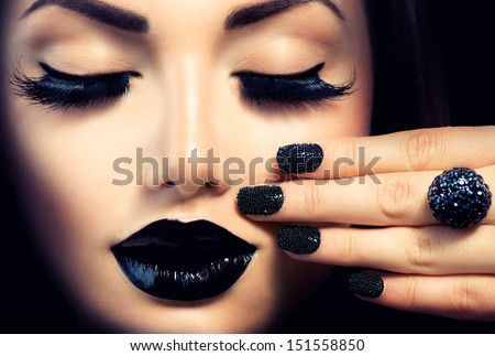 Beauty Fashion Model Girl with Black Make up, Long Lushes. Fashion Trendy Caviar Black Manicure. Nail Art. Dark Lipstick and Nail Polish. Isolated over black background - stock photo
