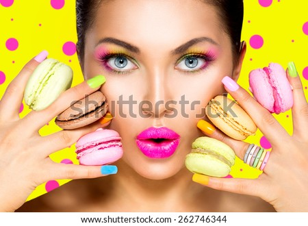 Beauty fashion model girl with colourful makeup and manicure taking colorful macaroons. Beautiful woman, bright make-up. Purple lipstick, vivid eyeshadow and accessories.Diet,dieting concept. Sweets. - stock photo