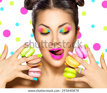 Beauty fashion model girl with colourful makeup and manicure taking colorful macaroons. Beautiful woman, bright make-up. Purple lipstick, vivid eyeshadow and accessories. Diet, dieting concept. Sweets - stock photo