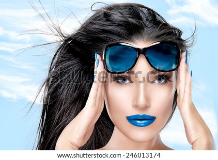 Beauty fashion model girl with healthy long hair in motion holding her blue sunglasses on forehead while looking at camera. Closeup portrait over blue sky. Beauty and fashion concept. - stock photo