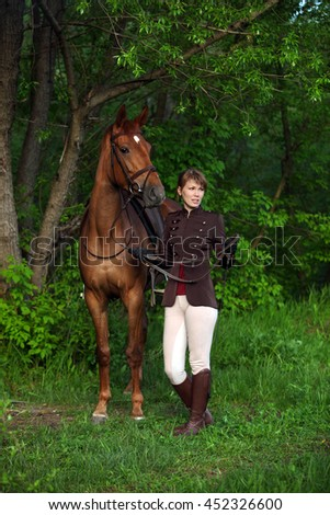 Beauty fashion model in equestrian hunt uniform posing with horse - stock photo