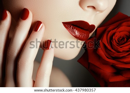 Beauty fashion model woman face. Portrait with red rose flower. Red Lips and nails. Beautiful woman with luxury makeup and manicure