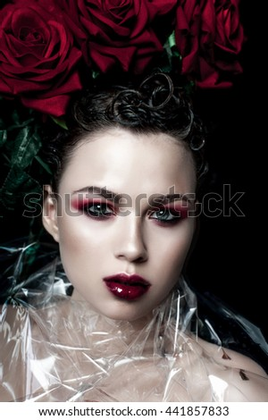 Beauty Fashion Model Woman face. Portrait with Red Rose flowers. Red Lips and Nails. Beautiful Brunette Woman with Luxury Makeup, perfect skin. girl in the image of rose with thorns