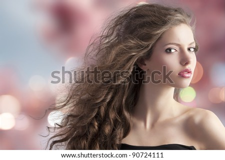 beauty fashion portrait of a very young cute brunette with long curly hair with hairstyle flying in the wind on cherry blossom bokeh background - stock photo
