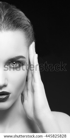Beauty fashion portrait of caucasian brunette woman wet wet red lipstick and arms touching face. Isolated on black background. Black and white - stock photo